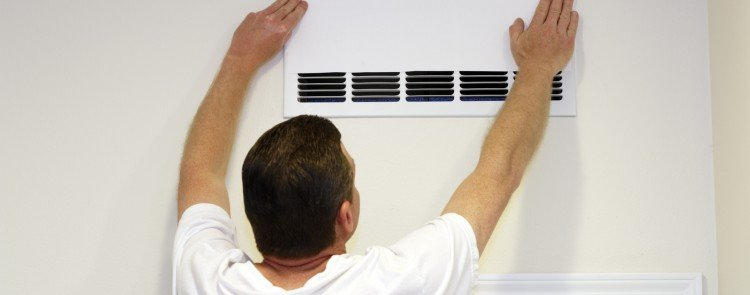 man placing cover over HVAC vent to improve the appearance