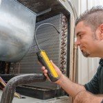 HVAC technician searching for a refrigerant leak on an evaporator coil